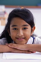 girl resting chin on folded hands