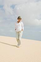portrait of mature woman walking barefoot on sandy beach