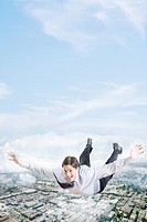 Young businessman flying over city
