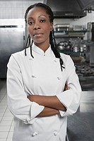 Female chef with arms crossed in kitchen portrait
