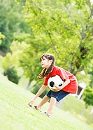 A girl playing with a soccer ball