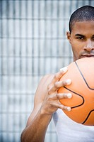 Portrait of a young African American man holding a basketball