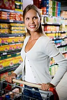 Woman with a trolley walking down a supermarket aisle