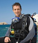 A male scuba diver sitting on a boat