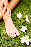 Close up shot of a woman´s feet in a tropical setting with frangipani