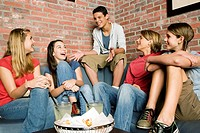 Group of teenage friends at a bowling alley, laughing and joking