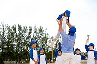 Young boy being lifted up by little league baseball coach