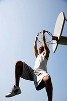 Portrait of young African jumping and hanging from a basketball ring