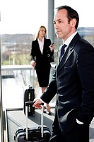 Businessman and businesswoman traveling, waiting in airport or station
