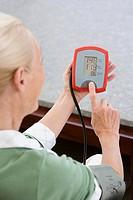 Woman using blood pressure gauge