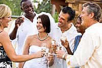 Multi_ethnic friends toasting newlyweds