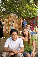 Hispanic sister and brother at outdoor party
