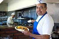 Hispanic waiter holding plate of food