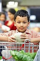 Indian boy holding fruit at grocery store