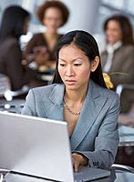 Asian businesswoman looking at laptop