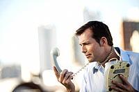 Man wrapping landline phone cord around neck, looking at receiver