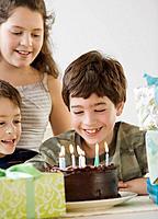 Hispanic boy looking at birthday cake