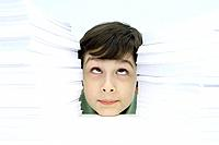 Boy resting head on table between two stacks of paper, rolling eyes