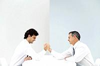Two businessmen arm wrestling, eyes closed, side view