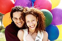 African couple hugging in front of balloons