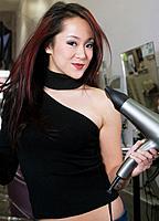 Asian hair stylist blow drying hair