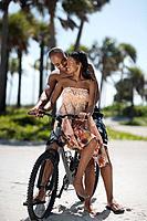 Multi_ethnic couple sitting on bicycle