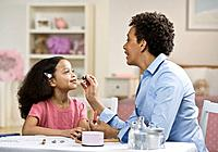 African mother applying lip gloss on daughter