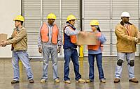 Multi_ethnic warehouse workers passing boxes