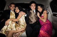 Multi_ethnic couples hugging in limousine