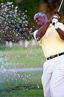 African man swinging golf club