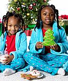 African sisters holding milk and Christmas cookies