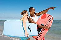 Multi_ethnic couple holding bodyboards