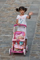 little girl with pushchair toy