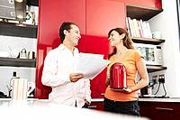 Couple discuss paperwork in kitchen