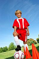 Boy 7_9 years soccer player holding foot on ball portrait