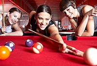 Three women playing pool and smiling