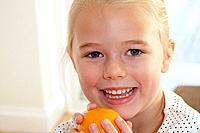 Young girl in kitchen holding orange and smiling