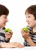 Two boys eating apples and smiling