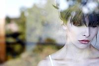 Shot of woman through windowpane thinking