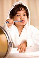 Mixed Race boy brushing teeth