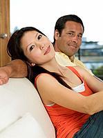 Multi_ethnic couple sitting on sofa