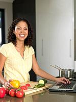 Mixed Race woman with laptop preparing food