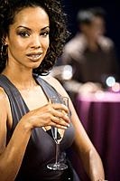 African woman holding glass of champagne