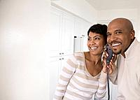 African couple talking on telephone