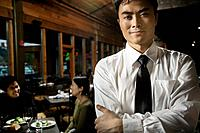 Asian waiter with arms crossed