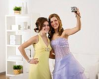 Multi_ethnic girls in prom dresses taking own photograph