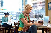 Woman using laptop computer in coffee shop