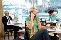 Woman using cell phone in coffee shop