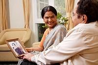 couple holding photograph, woman in bindi wearing sari