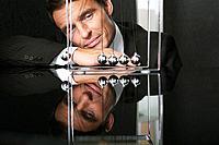 Businessman watching pendulum toy